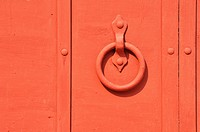 Red painted old iron door with circle doorhandle