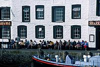 Harbour. Buildings,cafe. Sharks Fin Hotel. People seated against wall in sunshine. Mature people