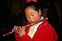 Naxi orchestra. Young woman playing woodwind instrument,flute.