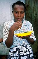 Woman eating fish with fingers. Yellow plate.