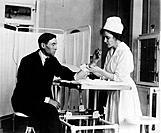 PUBLIC HEALTH SERVICE, c1920. /nA Public Health Service nurse treating a patient.