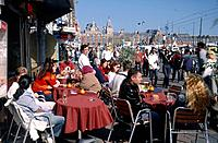 People sat at tables on the partially filled Damrak canal in the centre of Amsterdam that leads to the Centraal Station.