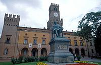 Near birthplace. Statue of composer Verdi. Building with tower. Gardens.