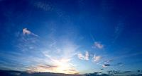Panoramic evening sky scape with a vivid blue open sky and gently setting sun far off on the distant horizon