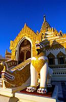 Burma. Buddhist temple. Central building,stupa,zedi. Yellow,gold colours. Entrance guardian statue,Nat.