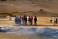 Volcanic,geothermal activity. Mud pools,steam vents. Group of people with cameras on walkway.