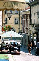 Town. Historic buildings. Cobbled street. Cafe,hotels. People eating,family with babybuggy.