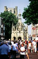 Cathedral city. Centre of town. Market Cross. Carved stone details. People,crowd.