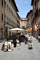 Street in historic town. Market stalls. Artwork on sale. Woman with child in pushchair.