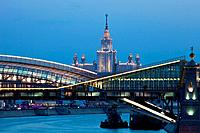 Russia, Moscow, Moscow State University and Pedestrian Bridge Rostovsky most linking Railway Station Kievsky Vokzal at dusk. The Stalinist University ...