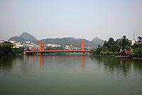 Guilin city is on the Li River,and has a large brightly painted red bridge at the centre of the city. The distinctive limestone karsts or rock formati...