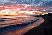 The breakwater and shoreline of the beach known as Puerto Cabopino,a part of the Marbella coastline at sunset. Marbella is one of the many seaside res...