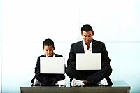 Asian father and son in business attire use laptops