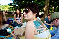 Woman with tattooed back holds bag of pitas at summer vegan picnic in city park.