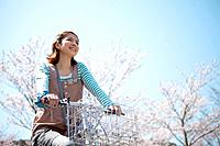 Young woman riding a bicycle near cherry trees