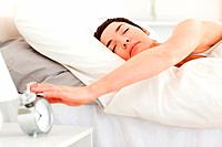 Serene woman turning off her alarm clock in her bedroom