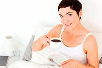 Close up of a woman drinking coffee in her bedroom