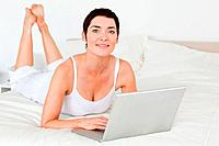Close up of a woman using a laptop in her bedroom