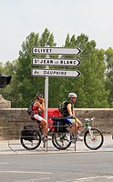 Two cyclists resting on a traffic direction signpost, Orleans, Loiret, France