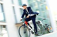 Mature businessman in suit riding bicycle, blurred motion