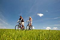 Young couple riding electric bicycle through field
