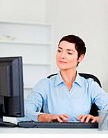 Portrait of a serious businesswoman typing wiht her computer in her office
