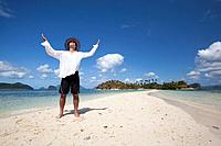 a tourist stands on the pure white sands of snake island, near el nido, bacuit archipelago, palawan, philippines