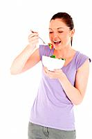 Beautiful woman eating a bowl of salad while standing against a white background