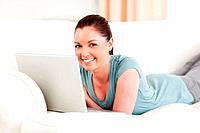 Good looking woman relaxing with her laptop while lying on a sofa in the living room
