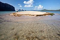a male tourist walks along the white sand on a small island near el nido, bacuit archipelago, palawan, philippines