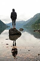 a young man stands on a rock in cameron lake, british columbia canada