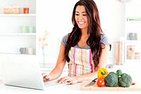 Gorgeous woman relaxing with her laptop while standing in the kitchen