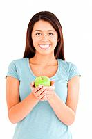 Attractive woman holding a green apple while standing against a white background