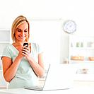 Cute woman with mobile and laptop smiling in the kitchen