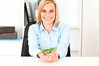 Woman holding a little plant smiies into camera in her office