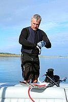 man putting on water skiing gloves on the back of a boat, troutdale oregon united states of america