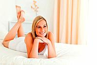 Serene woman posing on her bed while looking away from the camera