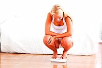 Fit woman on a weighing machine in her bedroom