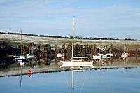boats moored in the water along the shoreline in winter near carrigaline, county cork ireland