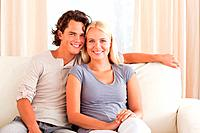 Smiling couple sitting on a sofa while looking at the camera