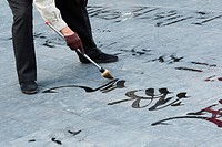 painting calligraphy on pavement at the temple of heaven, beijing, china