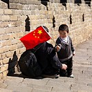 adult and child with chinese flag on the great wall of china, beijing, china