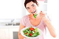 Good_looking woman eating salad in the kitchen