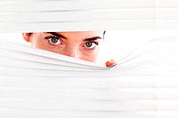 Brunette businesswoman peeking through a venetian blind in an office