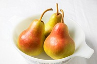 Three blush pears in a white dish