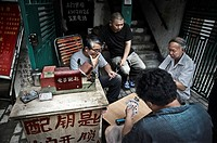 Men playing cards in the street of Shanghai. China country