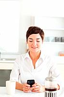 A woman sitting with her mobile phone and a coffee in the kitchen