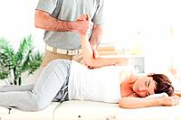 A chiropractor stretches a womans arm in his surgery
