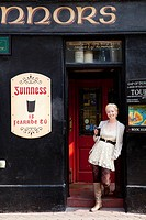 woman with a glass of guinness ale outside pub, killarney county kerry ireland