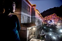 Woman look at the neon houses. Yellow Mountain monument. China country